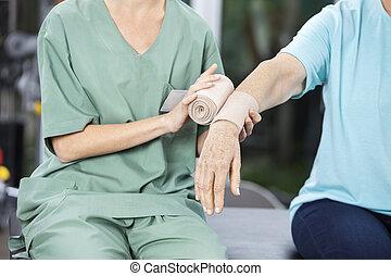 vrouwlijk, verpleegkundige, het putten, gummi verband, op, senior, vrouwenhand