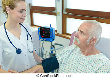 vrouwlijk, verpleegkundige, staand, door, senior, patiënt, in, rehab, centrum