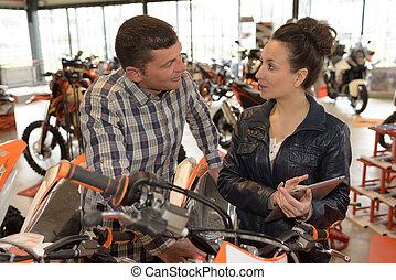 vrouwlijk, werktuigkundige, in, motorfiets, winkel