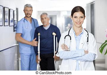 vrouwtje arts, staand, met, collega, en, senior, patiënt, in rug