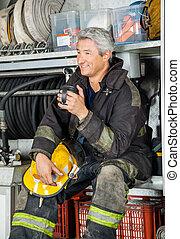 vuren truck, zittende , brandweerman, het glimlachen, station