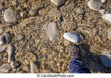 Wade - a hiking boot on a rock in the water stream of a ...