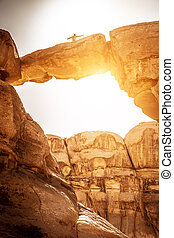Wadi Rum Desert, Jordan. Famous Um Frouth stone bridge, this place is very appreciated by tourists who climb the rocks to reach the top and pose for a unique photograph. backlight image.