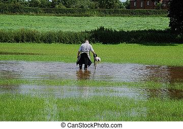 Wading Man - Man wading through flood waters on farmland...