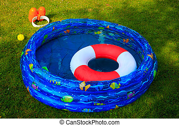 Documentary Picture of a wading pool and swim gear during a Beautiful summer day