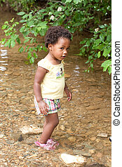A young African-American girl wading in a small stream.