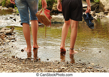 Two teenage girls cooling off their feet in a creek in the Belgian Ardennes