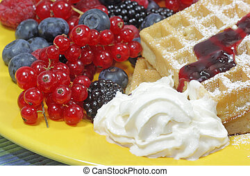 Wafers with fresh berries and whipped cream on a yellow ...