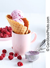 Waffle cone with raspberries and ice cream on wooden table