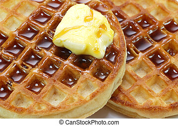 Closeup of waffles with syrup and butter.