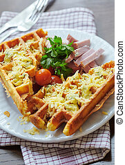 waffles covered with cheese with meat, parsley leaves on a plate