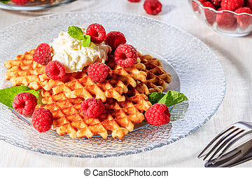 Waffles garnished with mascarpone and raspberries, selective focus.