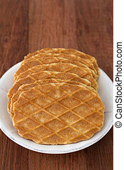 waffles in plate on brown background