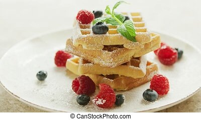 Waffles served on plate with berries - Fresh waffles served...