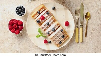 Waffles served on plate with berries - From above view of...