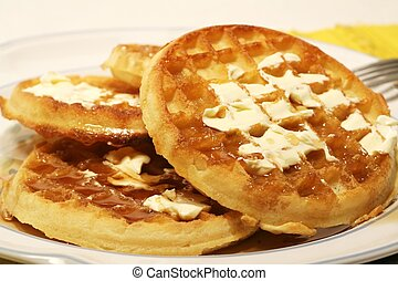Stack of waffles with butter and syrup