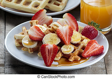 Waffles with bananas and strawberries covered with maple ...