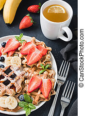 Waffles with berry fruit and cup of green tea