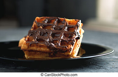 waffles with chocolate on a black plate dessert