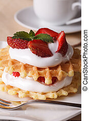 Waffles with fresh strawberry and cream close-up vertical