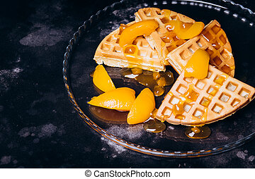 Waffles with peaches for breakfast on a black background.
