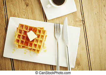 Waffles with syrup on white dish