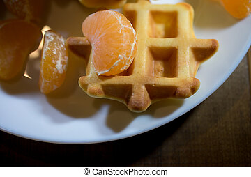 waffles with tangerines on a white plate