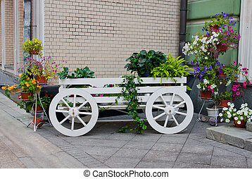 wagon with flowers near the wall