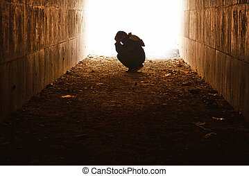 waif sitting in the tunnel in sorrow - head in the tunnel...