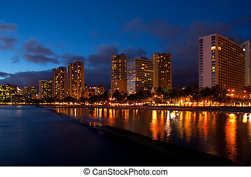 Waikiki's beautiful palm lined tourist beach is brightly lighted at night.