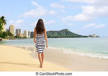 Waikiki beach vacation woman relaxing walking on sand at sunset. Honolulu travel destination in Oahu, Hawaii