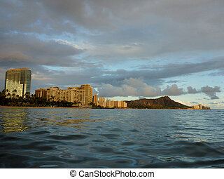 Waikiki Hotel building, clouds, and Diamond Head Crater in the distance on Oahu, Hawaii viewed from the water