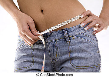 woman measuring her waist wearing blue jeans