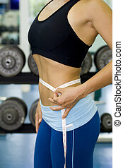 Waist Measurement 3 - A female fitness instructor measures...