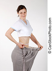 Waist Measurement - Young woman measures her waist after...