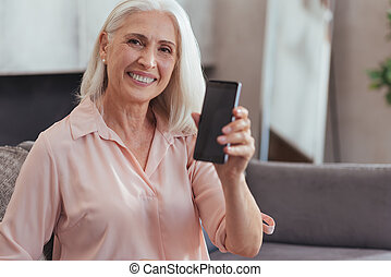 Delighted customer. Waist up of a cheerful aged woman holding her smart phone and showing it to you while sitting on the couch