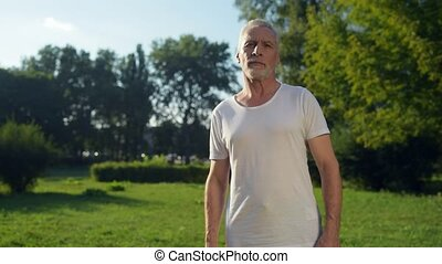 Waist up of a handsome aged man doing warm up exercises -...