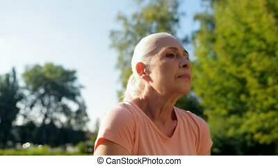 Waist up of a sporty aged woman warming up in the park -...