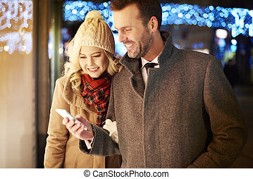 Waist up of couple using phone outdoors