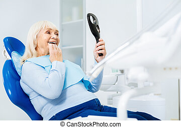 Cheerful smile. Waist up of delighted woman sitting on dental chair while looking in the dental mirror and being satisfied