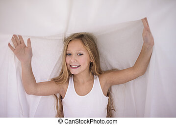 Waist up of little girl under the duvet