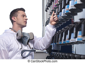 waist up of man selecting car paint. closeup of man wearing overall and working in shop