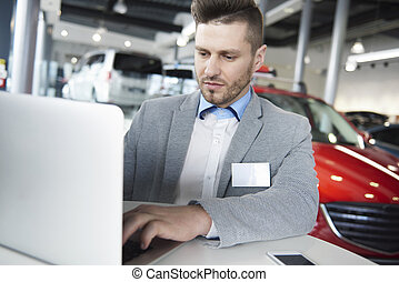 Waist up of salesman working on laptop