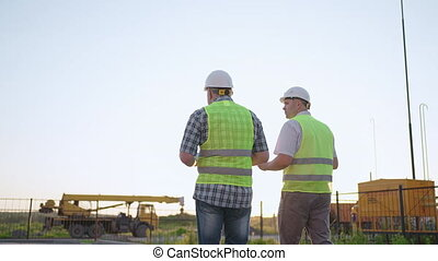 Waist-up of two middle-aged male builders wearing safety clothing, standing at construction site, man using walkie-talkie, his colleague holding paper with project plan