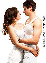 Waist up portrait of beautiful couple hugging, smiling and looking into each others eyes
