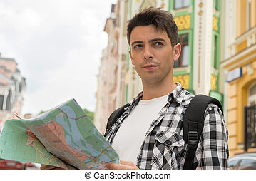 Waist-up portrait of handsome male traveler on the street holdin