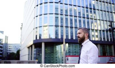 Waist up portrait of hipster businessman walking down the...