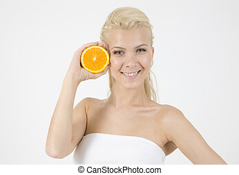 waist-up pose of model with slice of orange