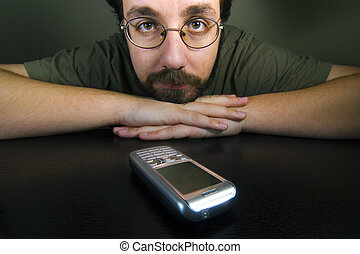 wait - man waiting for a call while the mobile is in the...