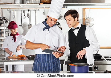 Chef and waiter using digital tablet with female chef working in restaurant kitchen